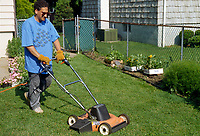 Man mowing lawn with electric push mower