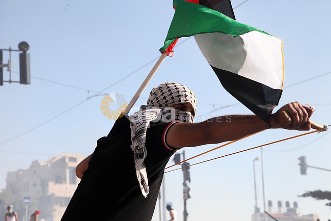 A masked Palestinian protester holds his national flag as he hurls stones towards Israeli police during clashes in the Shuafat neighborhood in Israeli-annexed Arab East Jerusalem, on July 3, 2014, one day after a Palestinian teenager was kidnapped and killed in an apparent act of revenge for the murder by militants of three Israeli youths. Photo by Saeed Qaq