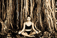 Woman meditating near a banyan tree