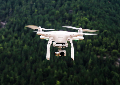 Drone with camera mount at flight with a forest background