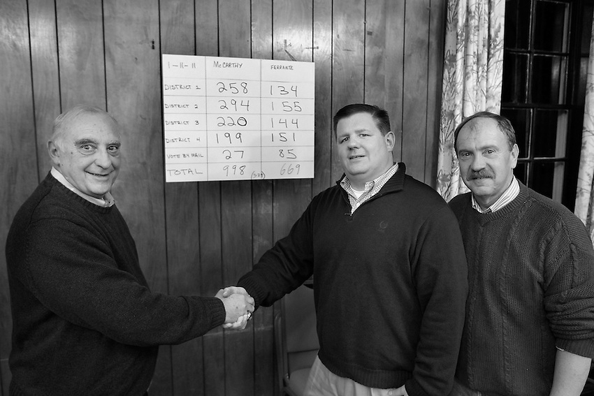Manasquan Mayor George Dempsey, (l to r) councilman-elect Owen McCarthy and councilman Ed Donovan pose at the tote board at the Squan Democratic Headquarters after McCarthy wins a special runoff election for borough council seat on Tue., Jan. 11, 2011.
