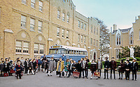 Saint John Villa Academy, NY. Large groups of children waiting for the bus in front of the school.