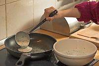 Mädchen, Kind verarbeitet Kräuter, Kräuter-Pfannkuchen mit Löwenzahn - Blättern und Gänseblümchen - Blüten, Pfannkuchen werden in der Pfanne gebraten, Taraxacum, Bellis perennis