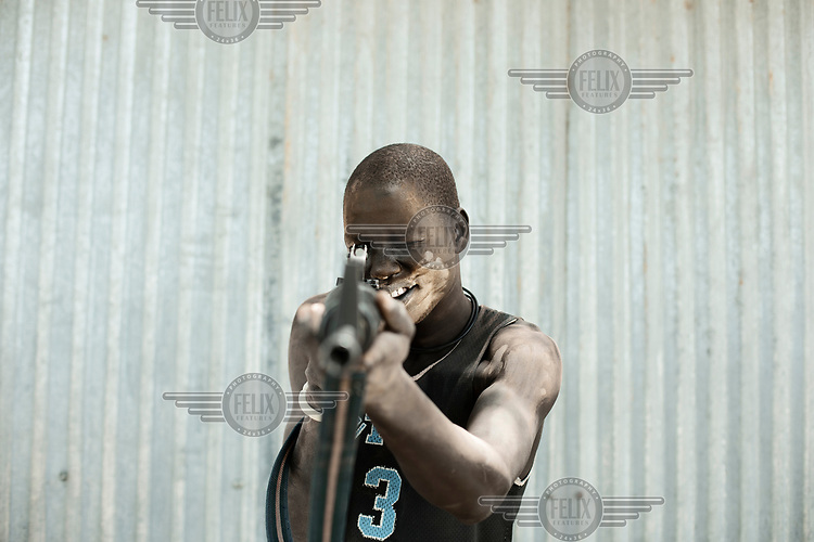 Mading Nhial (25), his face and body smeared with ashes, holds the rifle he uses to protect his cattle.