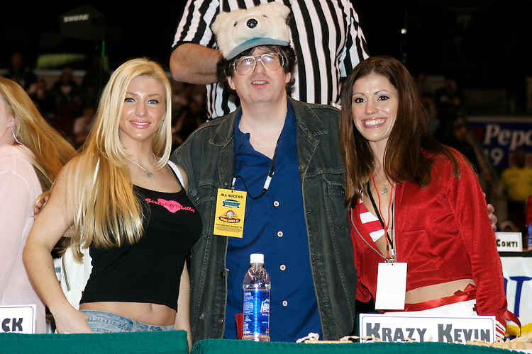 """Krazy Kevin and his allotment of Wingettes at the 13th annual Wing Bowl, held in Philadelphia on February 4, 2005 at the Wachovia Center.<br /> <br /> The Wing Bowl is a competitive eating event in which eaters try and down the most hot wings in 30 total minutes in front of a crowd of 10,000 plus people.  The real show however is all around the eaters, from the various scantily clad women, known as """"Wingettes"""", that make up competitors' entourages to the behavior of the fans themselves."""