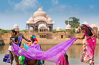 Indian family with colorful clothes in front of the iconic Kusum Sarovar, on the holy Govardhan Hill near Mathura, Uttar Pradesh, India