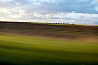 Blurred landscape seen from a speeding car on a country road, France.
