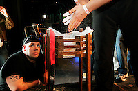 """Dan Fortuna looks on as a fellow arm wrestler applies chalk to his hands for better grip at the 28th Annual Big Apple Grapple, held in New York City on March 19, 2005.  The tournament is the first in the 2005 New York Arm Wrestling Association's """"Golden Arm Series""""."""