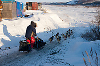 Bruce Linton runs down a ramp and onto the Unalakleet slough ice after leaving Unalakleet in Arctic Alaska during the 2010 Iditarod