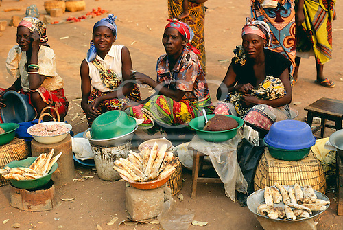 Kapata, Zambia. Colourfully dressed women sitting at a market selling their produce.