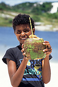 Salvador, Bahia, Brazil. Smiling boy holding a coconut with a straw in it, ready to drink.