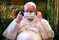 """Pope Francis puts on his mask during the meeting, """"Faith and Science: Towards COP26,"""" with religious leaders in the Apostolic Palace at the Vatican Oct. 4, 2021. The meeting was part of the run-up to the U.N. Climate Change Conference, called COP26, in Glasgow, Scotland, Oct. 31 to Nov. 12, 2021."""