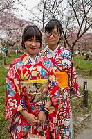 Japan, Kyoto, Hirano Shrine. Shinto shrine and garden with cherry blossoms. Girls in kimonos.
