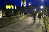 the bridge across the l'Aude river with two men walking across the bridge. Motion blur. Town of Limoux. Limoux. Languedoc. Illuminated at evening time and night. France. Europe.