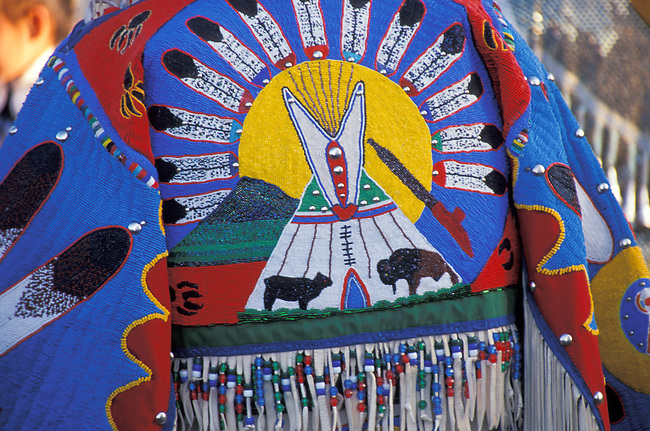 Colorful beadwork of a tepee, rising sun and 2 buffalo decorates the back yoke of a Blackfeet ladies pow wow regalia