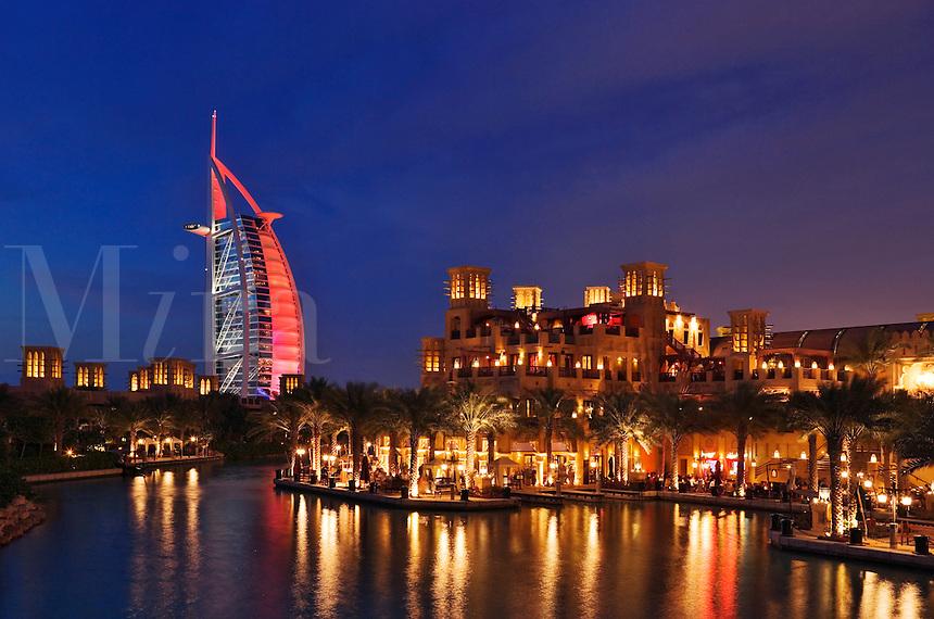 Burj al Arab Hotel, an icon of Dubai built in the shape of the sail of a dhow, stands on an artificial island just off Jumeirah Beach. View across Madinat Jumeirah.  Evening. Dubai. United Arab Emirates.
