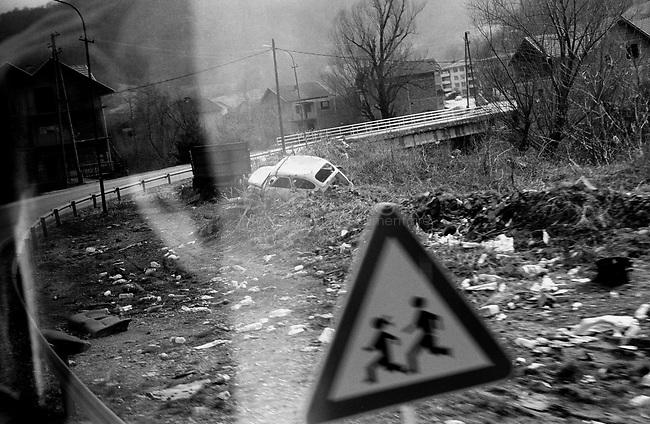 BOSNIA-HERZEGOVINA, Belgrade-Sarajevo Road, 03/2003..Lanscape pictures taken from the bus between Belgrad and Sarajevo. .In the streets of Nova Kasaba, small village in the ex muslim enclave. A car destroyed during the war is still allong the road.  .BOSNIE-HERZEGONVINE, Route Belgrade-Sarajevo, 03/2003..Photo prise depuis le bus qui relie Belgrade à Sarajevo. Dans les rues de Nova Kasaba, petit village de l'ancienne enclave musulmane. Une voiture détruite pendant la guerre a été abandonnée le long de la route..© Bruno Cogez