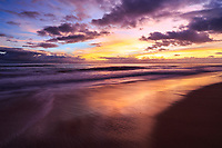The ocean and wet sand reflect the colors of a sunset sky at Kekaha Beach, Kaua'i.