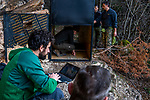 Balkan Lynx (Lynx lynx balcanicus) biologist, Alexander Pavlov, checking camera trap photos with former hunter turned conservationist, Plumb Mustafa, with biologists, Lilli Middelhoff, Eko Veapi, and Dime Melovski, maintaining box trap, Mavrovo National Park, North Macedonia