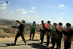 Israeli soldiers in riot gear walk toward Palestinian demonstrators during a protest against the controversial Israeli separation barrier on July 31, 2009 in the West Bank village of Bilin near Ramallah. Israeli troops sprayed the protesters with contaminated water which induced vomiting; others had to be treated for the effects of tear gas inhalation. The non-violent Bilin demonstration occurs weekly, as villagers march to the separation wall after midday friday prayers. photo by Issam Rimawi