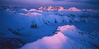 Aerial view of alpenglow from a setting sun, highlighting mountain ridgelines, with a cloud-filled valley below. Distant mountain at center rear is Mount Fernow. The North Cascades Mountain Range was formed by a combination of volcanic forces interacting with sedimentary rock formations. Washington State.Taken on 6X12 format Velvia 100 film.