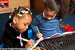 Education preschool 3-4 year olds pretend play two girls writing, computer keyboard nearby
