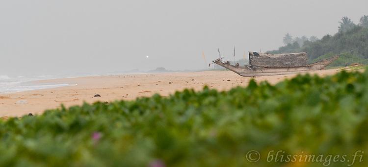 Old fishing canoe on beach at dawn. Barberyn (Beruwala) light shines through the humid sea-haze at dawn -Bentota, Sri Lanka