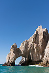 Sea of Cortez, Cabo San Lucas, Mexico; the Arch of Cabo San Lucas is illuminated by morning sunlight on a clear, blue sky day, these rocks at the southern most end of the Baja Peninsula separate the Sea of Cortez from the Pacific Ocean