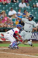 Round Rock Express catcher Luis Martinez #14 catches the ball as Tucson baserunner Vince Belnome #2 slides home during the Pacific Coast League baseball game against the Tucson Padres on August 4th, 2012 at the Dell Diamond in Round Rock, Texas. Belnome was called out but the Padres defeated the Express 10-6. (Andrew Woolley/Four Seam Images).