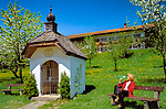 Deutschland, Bayern, Oberbayern, Chiemgau: Frau ruht auf Bank trinkt Mineralwasser, Kapelle, Blumenwiese und Apfelbluete | Germany, Bavaria, Upper Bavaria, Chiemgau: woman sitting on bench drinking from waterbottle, chapel, flower meadow and fruit tree blossom