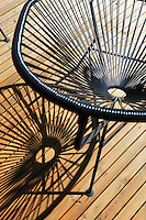 Detail of an Acapulco chair and its shadow on the roof terrace of this modern house