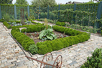 Upscale vegetable garden with farm antique tool ornament, cut stone walkway, fence, trellised apple fruit trees