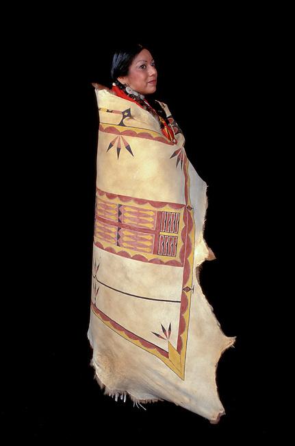 Shoshone female tribal member dressed in a traditional painted elk hide robe