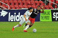 WASHINGTON, DC - SEPTEMBER 27: Lee Nguyen #42 of New England Revolution battles for the ball with Ola Kamara #9 of D.C. United during a game between New England Revolution and D.C. United at Audi Field on September 27, 2020 in Washington, DC.