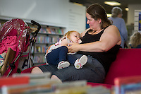 """A mother breastfeeding her toddler in a library.Image from the breastfeeding collection of the """"We Do It In Public"""" documentary photography picture library project: <br />  www.breastfeedinginpublic.co.uk<br /> <br /> <br /> Hampshire, England, UK<br /> 19/06/2015<br /> <br /> © Paul Carter / wdiip.co.uk"""