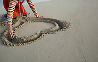 A young lady drawing a heart symbol on the beach during daytime of the holiday season.
