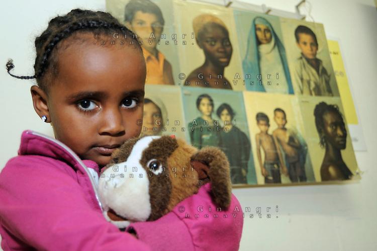 bambina della Somalia e i giocattoli, nel centro per asilanti, richiedenti asilo politico,in un ex bunker a Biasca, Canton Ticino, Svizzera.