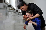 Demka Ramadanovic, a Roma boy whose family was displaced by a severe cold spell, gets help washing his face from Juntena Iseni, another displaced person, in a temporary shelter established by the Red Cross in Smederevo, Serbia. Church World Service has provided these and other affected families with food and other emergency supplies.