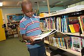 MR / Schenectady, NY. Zoller Elementary School (urban public school). Kindergarten classroom. Boy (5) looks at book in school library. MR: Abd2. ID: AM-gKw. © Ellen B. Senisi.