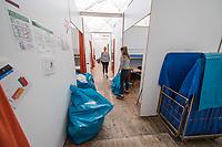 """Die letzten Fluechtlinge verlassen die Notunterkunft Kruppstrasse.<br /> Am Montag den 24. Juli 2017 zogen die letzten gefluechteten Menschen aus der Notunterkunft der Berliner Stadtmission in der Moabiter Kruppstrasse aus. Die Traglufthalle war im November 2014 als Notunterkunft errichtet und ist dann als Dauereinrichtung betrieben worden. Ohne Privatsphaere lebten manche Gefluechtete dort bis zu zwei Jahre. Nun wurden die Menschen in andere Unterkuenfte verteilt und der """"Ballon"""", wie er von den Bewohnern genannt wurde, wird abgebaut.<br /> Im Bild: Mitarbeiterinnen und freiwillige Helfer raeumen die Notunterkunft auf und bauen die Schlafkojen ab.<br /> 24.7.2017, Berlin<br /> Copyright: Christian-Ditsch.de<br /> [Inhaltsveraendernde Manipulation des Fotos nur nach ausdruecklicher Genehmigung des Fotografen. Vereinbarungen ueber Abtretung von Persoenlichkeitsrechten/Model Release der abgebildeten Person/Personen liegen nicht vor. NO MODEL RELEASE! Nur fuer Redaktionelle Zwecke. Don't publish without copyright Christian-Ditsch.de, Veroeffentlichung nur mit Fotografennennung, sowie gegen Honorar, MwSt. und Beleg. Konto: I N G - D i B a, IBAN DE58500105175400192269, BIC INGDDEFFXXX, Kontakt: post@christian-ditsch.de<br /> Bei der Bearbeitung der Dateiinformationen darf die Urheberkennzeichnung in den EXIF- und  IPTC-Daten nicht entfernt werden, diese sind in digitalen Medien nach §95c UrhG rechtlich geschuetzt. Der Urhebervermerk wird gemaess §13 UrhG verlangt.]"""