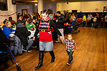 WATERBURY, CT. 21 December 2019-122119BS295 - Leslie Stevens, all decked out as Santa's favorites walks with Leandre Taylor, 2 1/2, during a Christmas Party for the less fortunate and homeless at the Basilica of Immaculate Conception in Waterbury on Saturday. Bill Shettle Republican-American