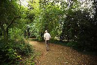 Old man walks on path through urban park. England