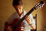 Cuba, Havana, Young music student learning classical guitar at a Music Academy, Vedado district, Central America,.