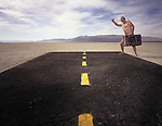 Nude hitchhiker with his suitcase at the end of the road in Black Rock Desert, Nevada.