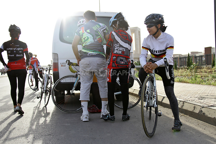 SULAIMANIYAH, IRAQ: Professional cyclist Nyan Yassin (far right) prepares for an evening training session with her club in Sulaimaniyah.<br /> <br /> Nyan Yassin, 24, is a professional competitive cyclist in Sulaimaniyah in the semi-autonomous region of Iraqi Kurdistan.  She is the captain of an all-female club called Newroz Club, which is the only cycling club for women in Sulaimaniyah, although there are other clubs around Iraq.  She trains and competes on roads that are badly surfaced and busy with traffic.<br /> <br /> Nyan was the first woman to start cycling in Sulaimaniyah.  She was always competitive and after trying her hand at different sports she settled on cycling.  She is now the top female cyclist in Iraq.  Her nickname is MigMig after the noise made by the cartoon character Roadrunner.<br /> <br /> Despite being clearly talented at her sport Nyan knows that in a couple of years she will have to get married and then abandon it as, in the traditional society that Kurdistan is, being a wife and a competitive sportswoman at the same time is not an option.<br /> <br /> Photo by Gona Hassan/Metrography