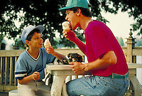 After baseball practice in baseball uniform boy aged 10 eats ice cream with father. father and son or coach and little leaguer.