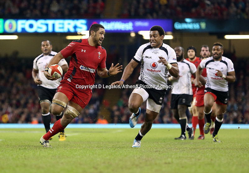 Pictured: Taulupe Faletau (L) against Waisea Nayacalevu of Fiji (R) on his run for a try for Wales. Saturday 15 November 2014<br /> Re: Dove Men Series rugby, Wales v Fiji at the Millennium Stadium, Cardiff, south Wales, UK.
