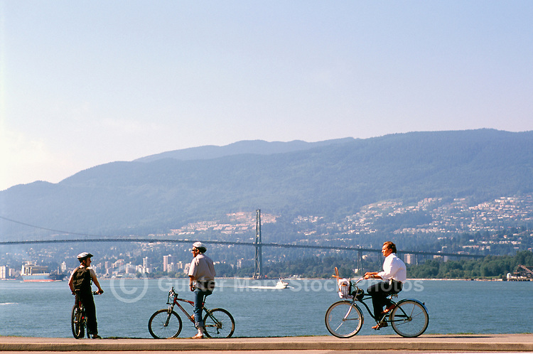 Stanley Park, Vancouver, BC, British Columbia, Canada - People cycling on Seawall along Burrard Inlet in Summer - Lions Gate Bridge, West Vancouver, and North Shore Mountains in background