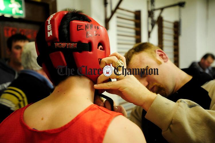 Coach Pat McDonagh checks his fighters head gear at Ennis Boxing Club.Pic Arthur Ellis.
