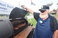 SLOW SMOKED TO PERFECTION <br />Bill Mudd smokes racks of ribs on Saturday July 16 at the Rogers American Legion Post 100 annual rib sale. Customers preordered racks or half-racks of ribs that they picked up Saturday afternoon at post headquarters, 711 W. Persimmon in Rogers. Mudd and his cooking crew use a dry-rub on the ribs and smokes them using split oak firewood for several hours. Mudd is with the post's chapter of the Sons of the American Legion group for people with parents who were veterans. Profits from this year's rib sale benefit the Benton County Women's Shelter, Mudd said. Go to nwaonline.com/210718Daily/ to see more photos.<br />(NWA Democrat-Gazette/Flip Putthoff)